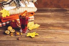 Bebida quente das maçãs e as bagas, a sangria no vidro e uma pilha de roupa feita malha em um fundo de madeira Conceito do outono foto de stock royalty free