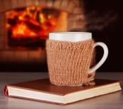 Bebida quente em vestir da caneca roupa feita malha, livros velhos Imagem de Stock