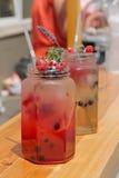 Bebida refrigerada com framboesas e corintos no frasco Imagens de Stock Royalty Free