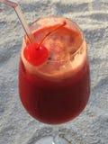 Bebida roja de la fruta, en la arena blanca Fotografía de archivo