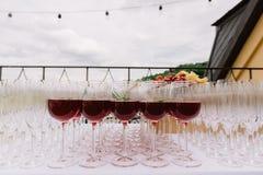 Bebida roja en las copas para el abastecimiento de la boda Imagenes de archivo