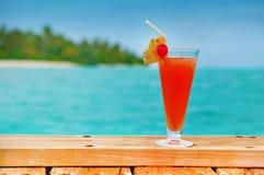 Bebida roja en una playa foto de archivo