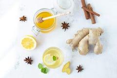 Bebida sana del jengibre en una taza Raíz del jengibre, miel en un tarro, limón en una tabla blanca imagen de archivo