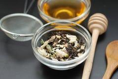 A bebida saudável do chá erval de Acaccia na bacia e a peneira sobre o fundo preto copiam o espaço Bebida saudável, frialdade imagem de stock