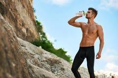 Bebida sedienta caliente del agua potable del hombre después de correr al aire libre Deporte foto de archivo libre de regalías