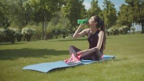 Bebida sorvendo da energia da mulher asiática apta na esteira do finess video estoque