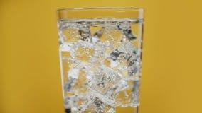 Bebida trasparent de colada El vidrio lleno de hielo frío de agua chispeante cubica amarillo almacen de video