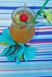 Bebida tropical con la fruta y el fondo azul del océano fotografía de archivo libre de regalías