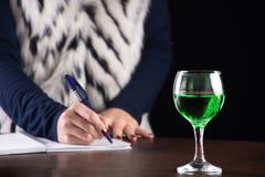 Bebida verde del ajenjo en cuaderno de la historia de la escritura del vidrio y de la mujer fotos de archivo libres de regalías