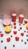 Bebida vermelha do batido no vidro com os ingredientes das bagas da palha e dos frutos no fundo de madeira branco, vista superior Imagens de Stock Royalty Free