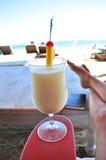 Bebida y libro tropicales en la playa Foto de archivo
