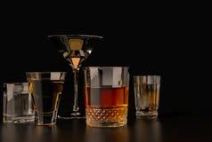 Bebidas alcohólicas fuertes, vidrios y vidrios, en presencia del whisky, vodka, ron, tequila, brandy, coñac en un viejo backg osc imagen de archivo libre de regalías