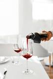 bebidas Close up do vinho tinto de derramamento da garrafa no vidro Imagem de Stock