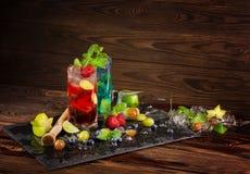 Bebidas coloridas com citrinas, bagas e hortelã Morango fresca e cocktail azuis da lagoa no fundo de madeira Fotografia de Stock