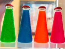 Bebidas coloridas fluorescentes da garrafa do aperitivo Imagens de Stock