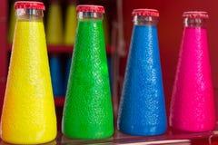 Bebidas coloridas fluorescentes da garrafa do aperitivo Imagem de Stock Royalty Free