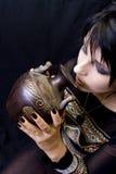 Bebidas de la mujer de Goth de un recipiente Imagenes de archivo