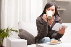Bebidas de la mujer mientras que mira su tableta fotografía de archivo