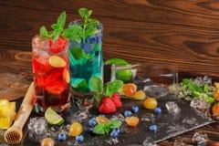 Bebidas del alcohol con las bayas en un fondo de madera Mojito frío con los arándanos, las fresas, la cal, la menta y el hielo Co Foto de archivo