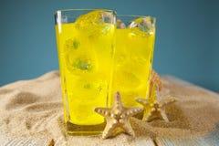 Bebidas del amarillo en fondo azul Fotografía de archivo