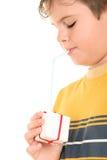 Bebidas del muchacho del regalo a través del túbulo Fotografía de archivo