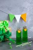 Bebidas del partido del día del ` s de St Patrick en botellas de vidrios en concre imagenes de archivo