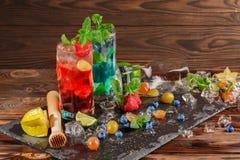 Bebidas do álcool com bagas em um fundo de madeira Mojito frio com mirtilos, morangos, cal, hortelã e gelo Copie o espaço Fotografia de Stock Royalty Free