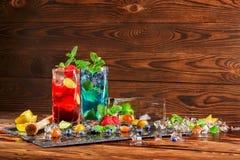 Bebidas do álcool com bagas em um fundo de madeira Mojito frio com mirtilos, morangos, cal, hortelã e gelo Copie o espaço Imagens de Stock