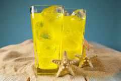 Bebidas do amarelo no fundo azul Fotografia de Stock