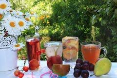 Bebidas do verão com fruto na janela aberta molhada ao jardim Limonada de refrescamento das cerejas, peras, uvas, pêssego com fru fotografia de stock