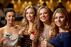 Bebidas felizes das mulheres nos vidros no clube noturno imagens de stock royalty free