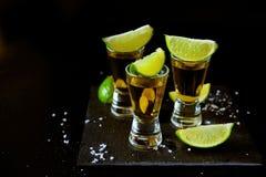 Bebidas fortes do álcool Tiros do Tequila com fatias de sal e de cal Imagens de Stock