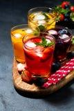 Bebidas frías de la fruta y de la baya en el surtido en fondo oscuro imagen de archivo libre de regalías