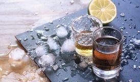 Bebidas fuertes alcohólicas en el fondo y los pedazos de cal fotografía de archivo libre de regalías