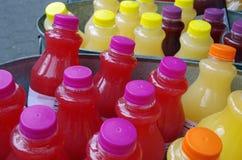 Bebidas heladas del jugo de las botellas en el hielo Imágenes de archivo libres de regalías