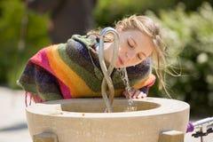 Bebidas rubias de la chica joven en la fuente pública Foto de archivo libre de regalías