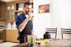 Bebiendo un smoothie verde en casa Imagen de archivo libre de regalías