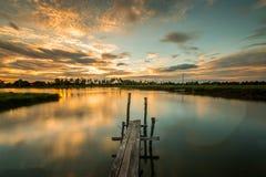 Beboste brug in de haven bij zonsondergang stock afbeelding