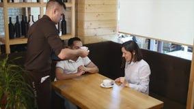 Bebouwd beeld die van de gelukkige jonge handen elkaar bekijken en van de paarholding, terwijl het zitten bij de koffie glimlache stock footage
