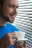 Bebouwd beeld die van de mens zich met kop van koffie bevinden Stock Foto