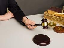 Bebouwd beeld die van rechter oordeel geven door houten hamer bij bureau te raken stock fotografie
