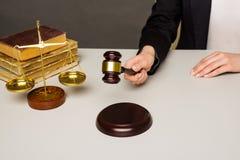 Bebouwd beeld die van rechter oordeel geven door houten hamer bij bureau te raken stock afbeelding