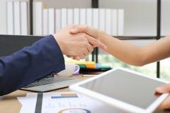 Bebouwd beeld van bedrijfsmensen die handen met partners na het be?indigen van een vergadering schudden De overeenkomstenconcept  stock afbeelding