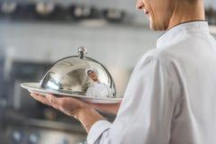 bebouwd beeld van de knappe plaat van de chef-kokholding met deksel stock foto's