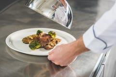 bebouwd beeld van de plaat van de chef-kokholding met maaltijd en deksel royalty-vrije stock afbeelding