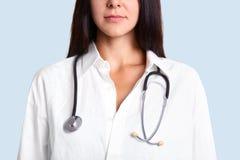 Bebouwd beeld van donkerbruine jonge vrouwelijke therapeut in witte toga met phonendoscope, tribunes die binnen, patiënten gaan d royalty-vrije stock fotografie