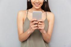 Bebouwd beeld van een gelukkige Aziatische vrouw met hoofdtelefoons Stock Afbeeldingen
