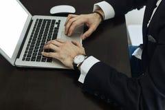 Bebouwd beeld van een jonge mens die aan zijn laptop achtermening van bezige gebruikende laptop van bedrijfsmensenhanden bij bure stock foto's