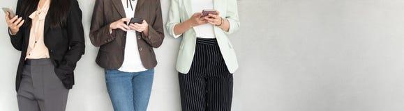 Bebouwd beeld van Groep Jonge Onderneemsters die smartphones terwijl status over grijze naakte muur gebruiken royalty-vrije stock foto