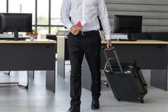 Bebouwd beeld van het paspoort en de bagage van de bedrijfsmensenholding in werkplaats van bureau Het concept van de zomervakanti royalty-vrije stock foto